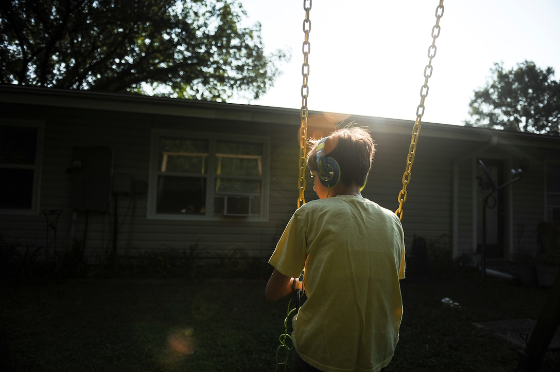 Morgan Jungk swings in her backyard Aug. 24, 2013, in Jacksonville, Ark. Morgan is the 14-year-old daughter of Master Sgt. Beth Jungk, a 19th Communications Squadron plans and programs manager, and suffers from autism, kabuki syndrome, severe epilepsy and other ailments. Swinging while listening to music is her favorite activity.(U.S. Air Force photo by Staff Sgt. Jake Barreiro)