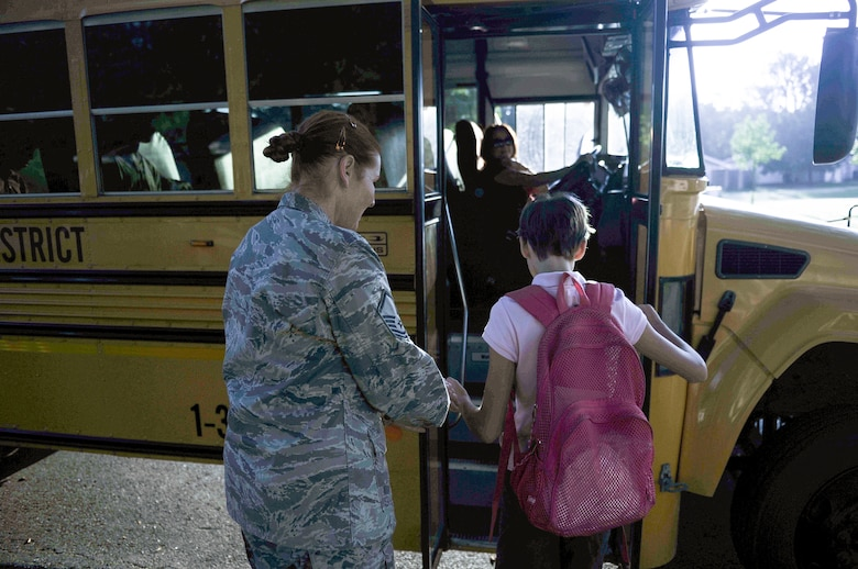 Master Sgt. Beth Jungk, a 19th Communications Squadron plans and programs manager, walks her daughter Morgan to her school bus Aug. 23, 2013, outside their home in Jacksonville, Ark. Getting Morgan ready for school on time in the morning is challenging for Beth, who has to get ready for work while making sure Morgan is taken care of. Beth is planning to retire from the military next year and hopes the change will provide more stability for her and Morgan. (U.S. Air Force photo by Staff Sgt. Jake Barreiro)