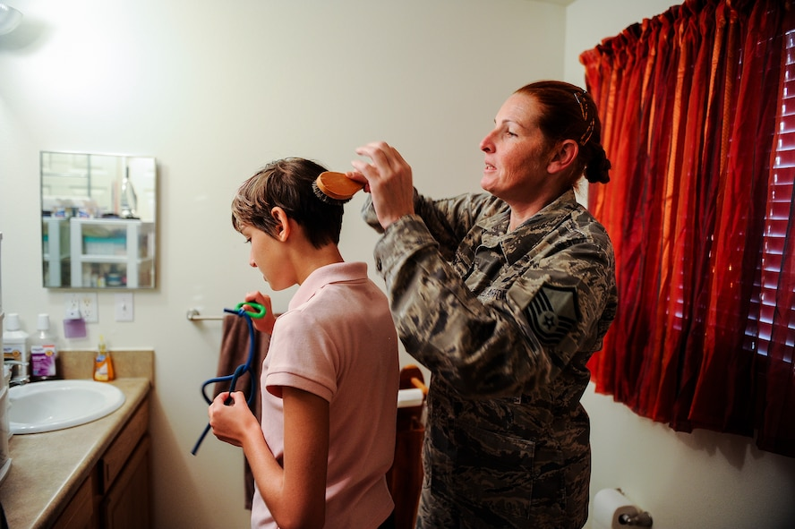 Master Sgt. Beth Jungk, a 19th Communications Squadron plans and programs manager, brushes her daughter, Morgan's, hair Aug. 23, 2013, at their home in Jacksonville, Ark. Beth has to fully clothe and groom Morgan every day before school in addition to getting ready for work herself. (U.S. Air Force photo by Staff Sgt. Jake Barreiro)