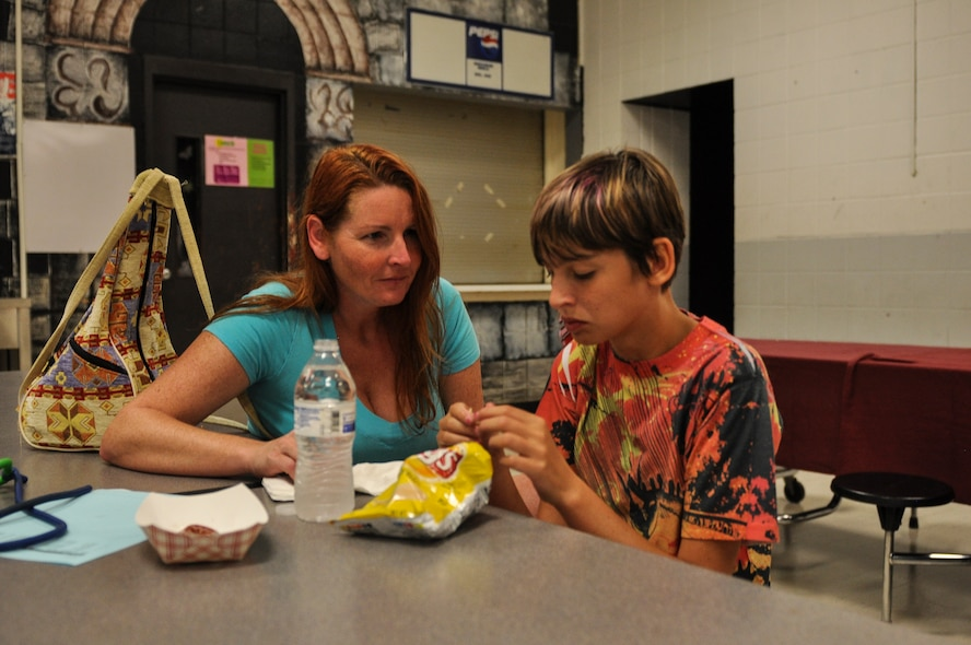 Morgan Jungk, daughter of Master Sgt. Beth Jungk, a 19th Communications Squadron plans and programs manager, eats by her mother during orientation night Aug. 15, 2013, at Northwood Middle School in Gravel Ridge, Ark. Beth tried to acclimate Morgan to the idea of going back to school by taking her to her classrooms and meeting her teachers. (U.S. Air Force photo by Staff Sgt. Jake Barreiro)