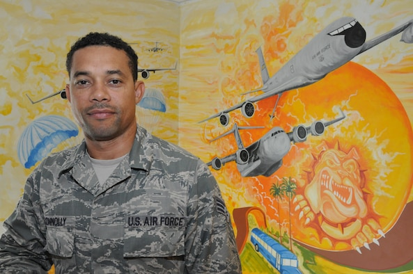 U.S Air Force Senior Airman Sean Connolly, air transportation specialist, 69th Aerial Port Squadron, poses in front of the mural he painted in the stairwell at the entrance of 69 APS here at Joint Base Andrews, Md. The mural highlights the different aspects of the aerial port mission and took more than six months for him to complete.