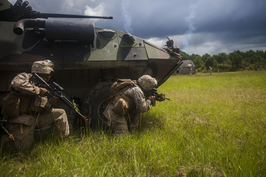 U.S. Marines with Battalion Landing Team (BLT) 1st Battalion, 6th Marine Regiment, 22nd Marine Expeditionary Unit's (MEU) light armored reconnaissance company raid a compound during a motorized raid course at Marine Corps Base Camp Lejeune, N.C., Aug. 20, 2013. Approximately 120 Marines in more than 20 light armored vehicles worked alongside Alpha Co., BLT 1/6, during the weeklong field exercise. The MEU is scheduled to deploy in early 2014 to the U.S. 5th and 6th Fleet areas of responsibility with the Bataan Amphibious Ready Group as a sea-based, expeditionary crisis response force capable of conducting amphibious missions across the full range of military operations. (U.S. Marine Corps photo by Sgt. Austin Hazard/Released)
