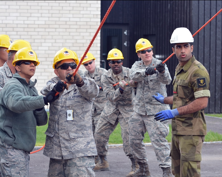 U.S. Air Force Staff Sgt. Liza McClaren (left) assists members of the 149th Civil Engineering Squadron, a subordinate unit of the Texas Air National Guard's 149th Fighter Wing, headquartered at Joint Base San Antonio – Lackland, Texas, assemble a steel-frame structure at the Norwegian Military Academy (Krigsskolen), at Camp Linderud, in Oslo, Norway, Aug. 13, 2013. McClaren, a financial program manager with the 149th Fighter Wing, was in Norway with the 149th Civil Engineering Squadron as part of the National Guard Bureau's deployment for training program. Also included in the photo is Cadet Aqeel Ahmed, the project manager. (This image was modified to obscure personally identifiable information on one of the subject's identification badge for security and privacy reasons.) (U.S. Air National Guard photo by Staff Sgt. Phil Fountain / Released)
