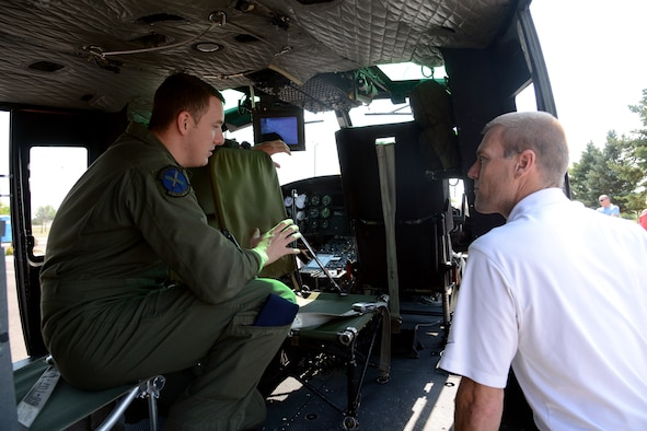 Staff Sgt. Justin Nissen, 40th Helicopter Squadron NCO in charge of current operations, shows Ken Coburn the inside of a UH-1N Huey helicopter. Coburn's father, Master Sgt. (Ret.) Joe Corburn, was a former 20th Helicopter Squadron Sikorsky CH-3C helicopter flight engineer (U.S. Air Force photo/Staff Sgt. R.J. Biermann)