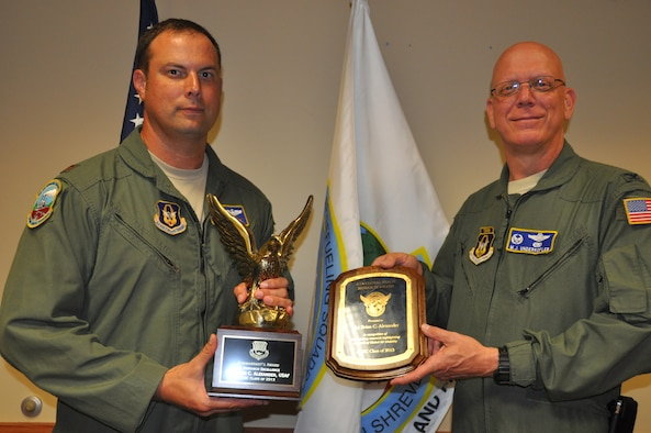Col. Michael Underkofler, 514th Air Mobility Wing commander, congratulates Maj. Brian Alexander, 78th Air Refueling Squadron KC-10 Extender pilot, for receiving the Air Command and Staff College's commandant's award for excellence in research here Aug. 25. Alexander, spent 16 weeks completing his research paper while in pursuit of his master's degree from Air Command and Staff College (U.S. Air Force photo/Senior Airman Chelsea Smith).