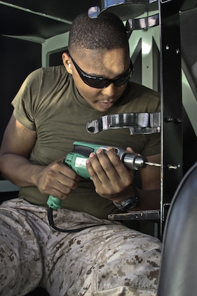Cpl. Davion Carroll, Marine Wing Support Squadron 171 motor transportation mechanic, does maintenance work on a 7-ton truck in the MWSS-171 warehouse at Marine Corps Air Station Iwakuni, Japan, Aug. 21, 2013. With only a handful of Marines left in MWSS-171 motor-T, their hardest task is completing their usual workload with less people.
