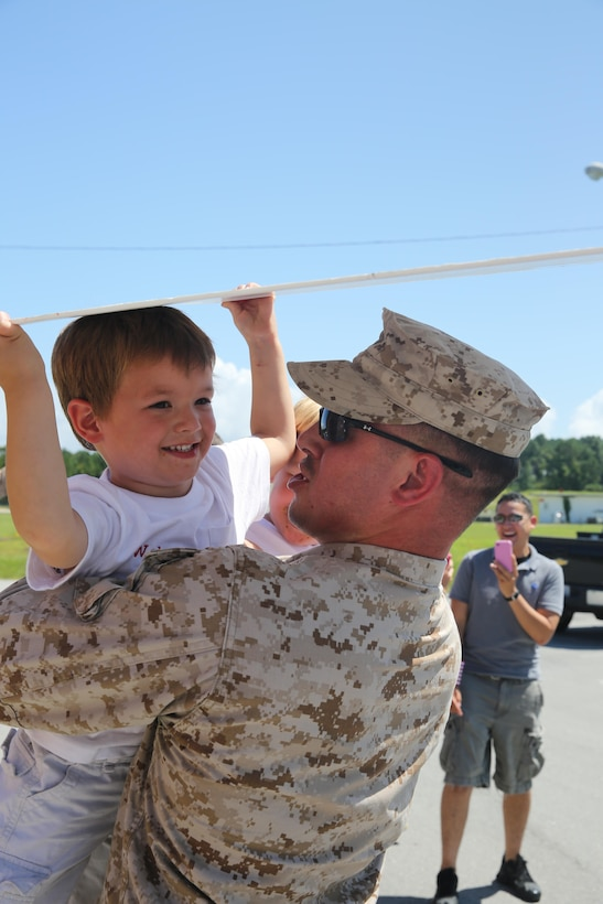 Cpl. Tyson Donaldson embraces his 3-year-old son after returning from a five-month deployment to Spain Friday. While deployed Donaldson, a communications technician with Marine Air Control Squadron 2, and seven other Marines attached to Marine Medium Tiltrotor Squadron 365 served as a Marine air traffic control mobile team.