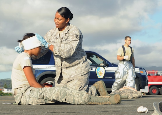 Staff Sgt. Yvette Baldwin gives first aid to a mock victim during a major accident response exercise Aug. 23, 2013, at Lajes Field, Azores. Baldwin is the NCO in charge of flight medicine at Lajes Field and is responsible for the care of Lajes' air traffic controllers and other Airmen whose day-to-day activities include occupational hazards. Baldwin is assigned to the 65th Medical Operations Squadron. (U.S. Air Force photo/Guido Melo)