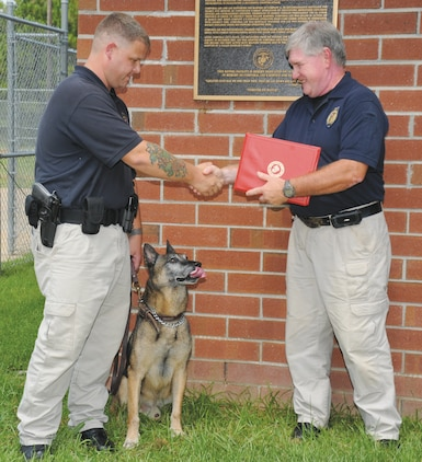 Randy Jack, chief of police, Marine Corps Police Department, right, presents Cpl. Christopher Gurr, Civilian Police Working Dog handler, MCPD, with a certificate for BarrosÕ distinguished service, Tuesday. Barros, a patrol/drug detector dog, retired after seven years during a ceremony at Corporal Dustin Jerome Lee Kennel and Gurr adopted him.