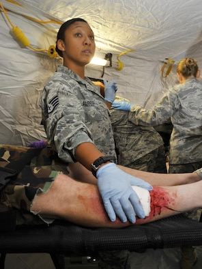 An U.S. Air Forces in Europe and Air Forces Africa medical unit member patches up the leg of a wounded patient during expeditionary medical support training Aug. 28, 2013, at Ramstein Air Base, Germany. EMEDS training is conducted to prepare Airmen for humanitarian missions. (U.S. Air Force photo/Airman Dymekre Allen)
