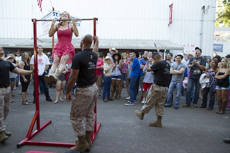 Rodeo attendees watch in awe as a participant attempts pull-ups during a Marine Corps pull-up challenge at the St. Paul Rodeo, St. Paul, Ore., July 3. The rodeo was a five day event full of bull rides, horse races and other competitions celebrating Independence Day. Participants receive Marine Corps gear for pull-ups successfully completed.