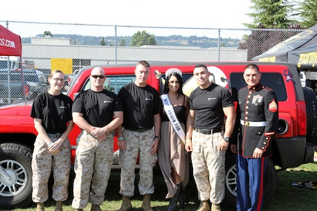 Gabrielle Neilan, Miss Oregon USA, takes a photo with Marines from Recruiting Station Portland, 12th Marine Corps District, during a Marine Corps pull-up challenge at Oregon Jamboree Music Festival in Sweet Home, Ore., Aug., 2. Participants receive Marine Corps gear for pull-ups successfully completed.