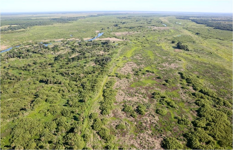 The historic Kissimmee River floodplain, north of Lake Okeechobee, is about 1-3 miles wide. This photo from May 7, 2013 is a view looking north in the Central Phase 1 Kissimmee River restoration area during late dry season conditions. The uplands start at the edge of the floodplain and the boundary is marked by Live Oaks, which show up as dark green areas at the top of the picture. The floodplain here is about 1.5 miles wide, and the water that collects here eventually flows into Lake Okeechobee.