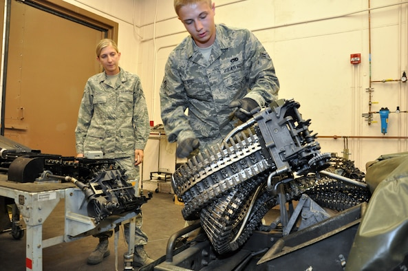 Staff Sgt. Angela Earp, 140th Wing conventional maintenance crew chief, left, supervises Airman 1st Class Cameron Dillavou, 140th Wing conventional maintenance crew member, as he lifts the adapter head of the Universal Ammunition Loading System before connecting it to the table Aug. 1, 2013, on Buckley Air Force Base, Colo.  The UALS hold 1,525 rounds of 20mm ammunition used by F-16 Fighting Falcons. The 140th Wing handles the munitions needs of units across the Front Range. (U.S. Air Force photo by Staff Sgt. Nicholas Rau/Released)