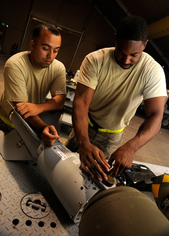 Senior Airman Jesse Bermudez and Staff Sgt. Everett Myles prepare the fin on a laser joint directed attack munition during a bomb build at the 379th Air Expeditionary Wing in Southwest Asia, Sept. 2, 2013. Bermudez is a 379th Expeditionary Maintenance Squadron conventional maintenance crew member and a San Antonio native. Myles is a 379th EMXS conventional maintenance crew chief and hails from Fort Worth, Texas. Both are deployed from Dyess Air Force Base, Texas. (U.S. Air Force photo/Senior Airman Bahja J. Jones)