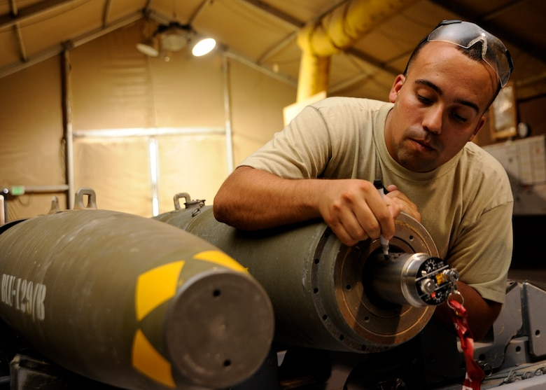 Senior Airman Jesse Bermudez writes the service life start date on a tail fuse during a bomb build at the 379th Air Expeditionary Wing in Southwest Asia, Sept. 2, 2013. Bermudez is a 379th Expeditionary Maintenance Squadron conventional maintenance crew member deployed from Dyess Air Force Base, Texas, and a San Antonio native. (U.S. Air Force photo/Senior Airman Bahja J. Jones)