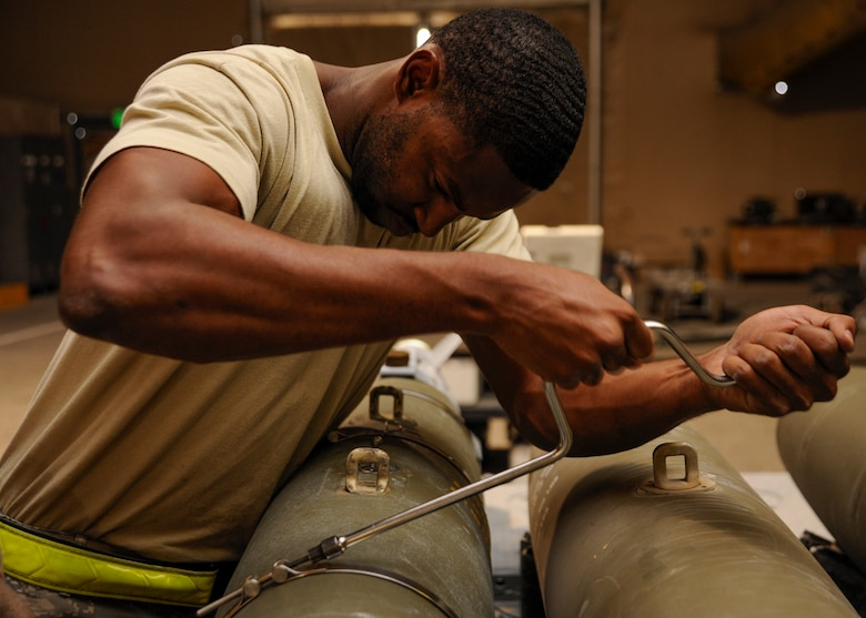 Staff Sgt. Everett Myles uses a speed handle to secure straps on a laser joint directed attack munition during a bomb build at the 379th Air Expeditionary Wing in Southwest Asia, Sept. 2, 2013. Myles is a 379th Expeditionary Maintenance Squadron conventional maintenance crew chief deployed from Dyess Air Force Base, Texas, and hails from Fort Worth, Texas. (U.S. Air Force photo/Senior Airman Bahja J. Jones)
