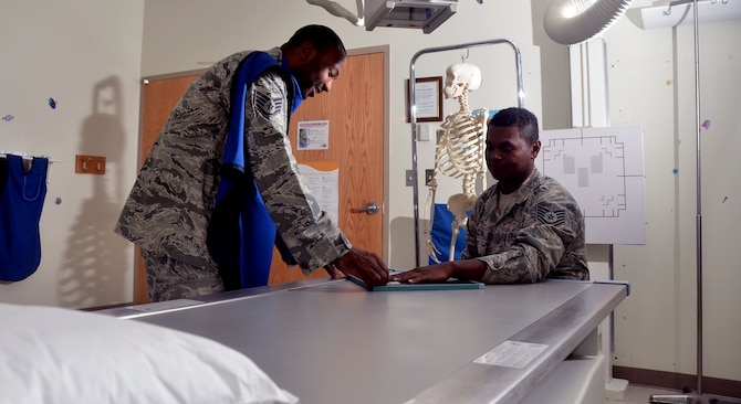 Staff Sgt. Jahmal Nicholas (left), 36th Medical Support Squadron NCO in charge of diagnostics imaging, positions Tech. Sgt. JJ McCloud, 36th MDSS diagnostic and therapeutic flight chief, for a posterior anterior hand x-ray during training Aug. 4, 2013, on Andersen Air Force Base, Guam. Andersen's clinic performs approximately 300 x-rays a month to allow a more in-depth look into any anomalies a patient may have. (U.S. Air Force photo by Airman 1st Class Mariah Haddenham/Released)