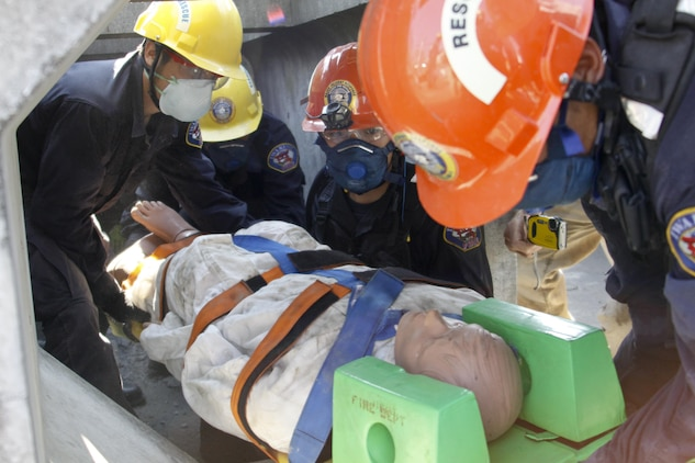 Firefighters from Marine Corps Air Station Iwakuni, Japan, extract a training dummy from a simulated collapse for their practical application exam during the Urban Search and Rescue Technical Search Training course Aug. 28, 2013.