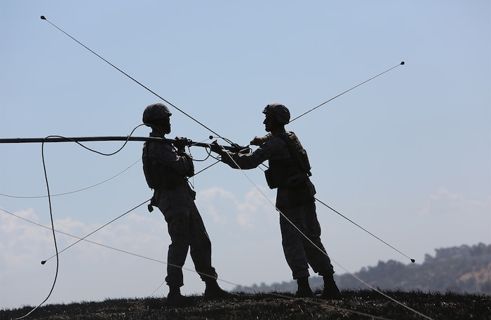 Field radio operators with Combat Logistics Battalion 5, 1st Marine Logistics Group disassemble a field antenna during a combat operations center exercise aboard Camp Pendleton, Calif., Sept. 5, 2013. The COCEX requires Marines to rapidly set up, disassemble and displace command nodes in an expeditionary environment.