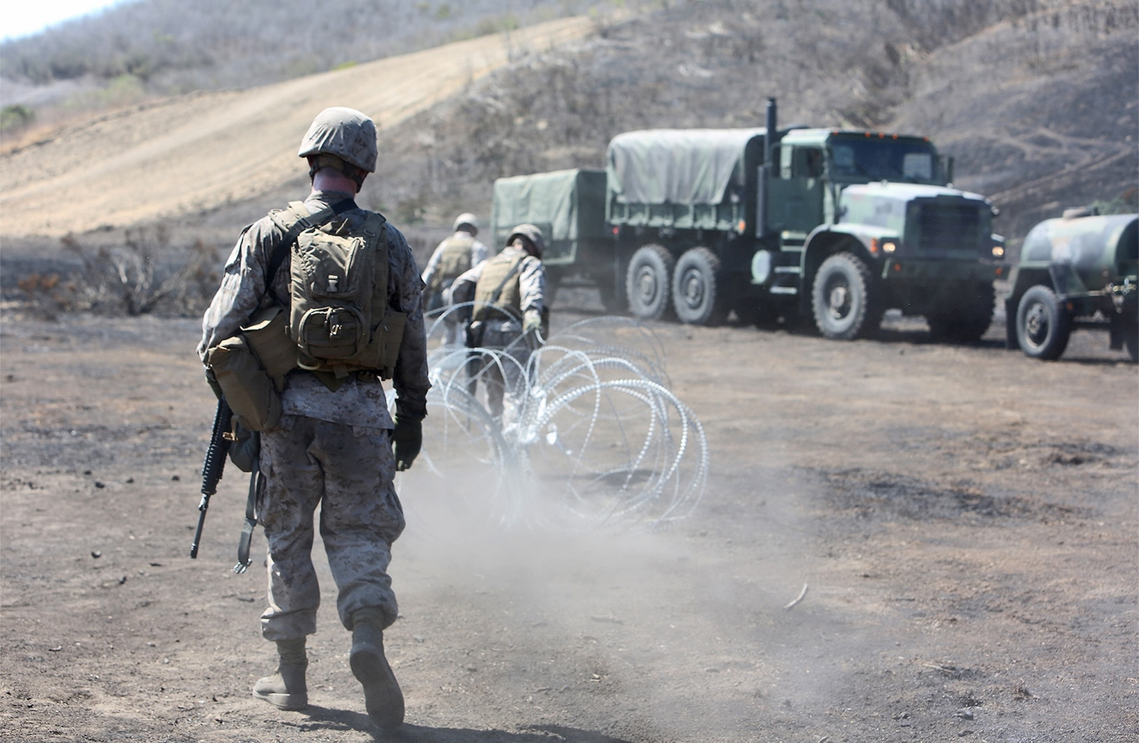 Marines with Combat Logistics Battalion 5, 1st Marine Logistics Group, set up a perimeter using concertina wire during a combat operations center exercise aboard Camp Pendleton, Calif., Sept. 5, 2013. The COCEX requires Marines to rapidly set up, disassemble and displace command nodes in an expeditionary environment.