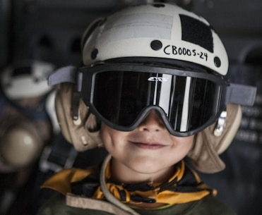 A child wears a cranial during Junior Jarhead Day hosted by Marine Aircraft Group 16 aboard Marine Corps Air Station Miramar, Calif., June 8. Crew chiefs took the children into an MV-22B Osprey and taught them about their job with the power of imagination.