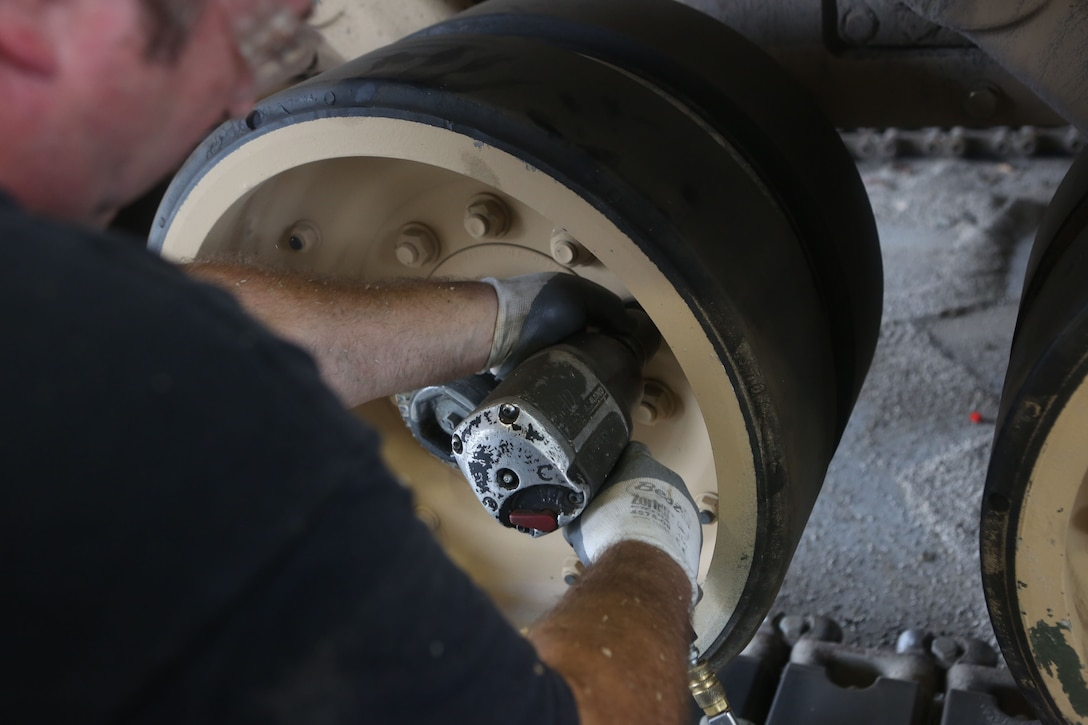 An Anniston Army Depot employee unscrews a wheel on an assault breaching vehicle belonging to 2nd Combat Engineer Battalion, 2nd Marine Division, in order to upgrade the vehicle aboard Marine Corps Base Camp Lejeune, Sept. 5, 2013. The tracks and wheels needed to be removed to upgrade the body frame of the vehicle with improved suspension.