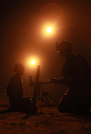 """Lance Cpl. Justin Downing (left) and Lance Cpl. Michael Delorme (right), both mortarmen with Weapons Platoon, Lima Company, 3rd Battalion, 3rd Marine Regiment, Marine Rotational Force - Darwin, prepare to fire a 60mm mortar, here, during Exercise Koolendong, Sept. 3. Throughout the exercise, MRF-D Marines conducted day and night live-fire training. This training evolution is the first of its kind, here, in which Marines with MRF-D and the 31st Marine Expeditionary Unit worked bilaterally with the Australian soldiers of Bravo Company, 5th Battalion, Royal Australian Regiment as a """"proof of concept"""" to assess the capacity of the training ranges to support a battalion-sized live-fire event."""