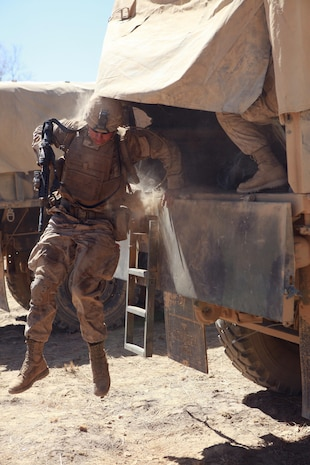 """A Marine with Lima Company, 3rd Battalion, 3rd Marine Regiment, Marine Rotational Force - Darwin, jumps out the back of a 7-ton truck during Exercise Koolendong, here, Sept. 3. MRF-D Marines traveled to the range either by foot, vehicle or aircraft. This training evolution is the first of its kind, here, in which Marines with MRF-D and the 31st Marine Expeditionary Unit worked bilaterally with the Australian soldiers of Bravo Company, 5th Battalion, Royal Australian Regiment as a """"proof of concept"""" to assess the capacity of the training ranges to support a battalion-sized live-fire event."""