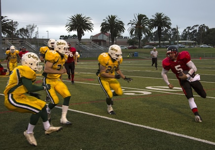 Casey Rogers, a quarterback with the Marine Corps Air Station Miramar Falcons, runs down the field during a game against the 3rd Assault Amphibian Battalion Gators at the Paige Field House aboard Marine Corps Base Camp Pendleton, Calif., Aug. 13. The Falcons' next game is against the 5th Marine Grizzlies on Aug. 27.