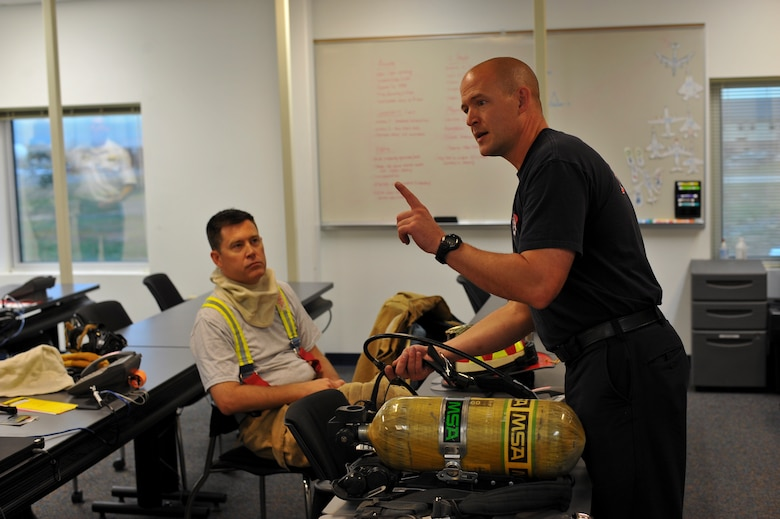 Jason Debord, Buckley firefighter, left, demonstrates the use of an air tank while Col. Dan Wright, 460th Space Wing commander, listens Sept. 5, 2013, at the Buckley Fire Department on Buckley Air Force Base, Colo. Wright, as well as Chief Master Sgt. Craig S. Hall, 460th SW command chief, and Lt. Col. Allen Thibeaux, 460th Civil Engineer Squadron commander, were brought through a fire immersion scenario designed to teach them the challenges firefighters face during an emergency.  (U.S. Air Force photo by Senior Airman Phillip Houk/Released)