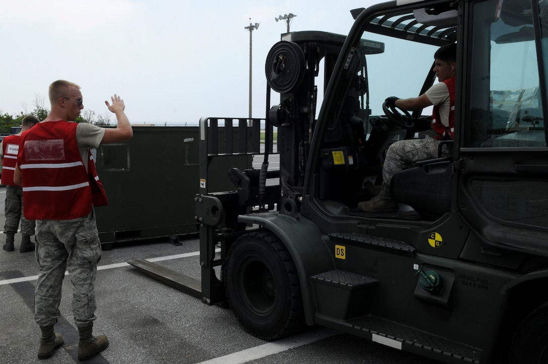 U.S. Air Force Airman 1st Class Kevin Nigh guides Airman 1st Class Bryan Orozco, as he uses a 10K forklift to move palletized equipment for a mock deployment as part of a local operational readiness exercise on Kadena Air Base, Japan, Sept. 9, 2013. The exercise is designed to test the readiness of Kadena Airmen. Nigh and Orozco are both vehicle maintainers assigned to the 18th Logistics Readiness Squadron. (U.S. Air Force photo by Senior Airman Marcus Morris)
