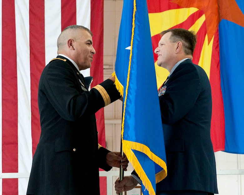 "U.S. Army Maj. Gen. Hugo Salazar, (left) the adjutant general of the Arizona National Guard, presents a general officer flag to Brig. Gen. ""Mick"" McGuire, commander of the 162nd Fighter Wing, Arizona Air National Guard at his promotion ceremony to Brigadier General in Tucson, Ariz., Sept. 7, 2013.  (U.S. Air National Guard photo by Tech. Sgt. Hollie Hansen/Released)"