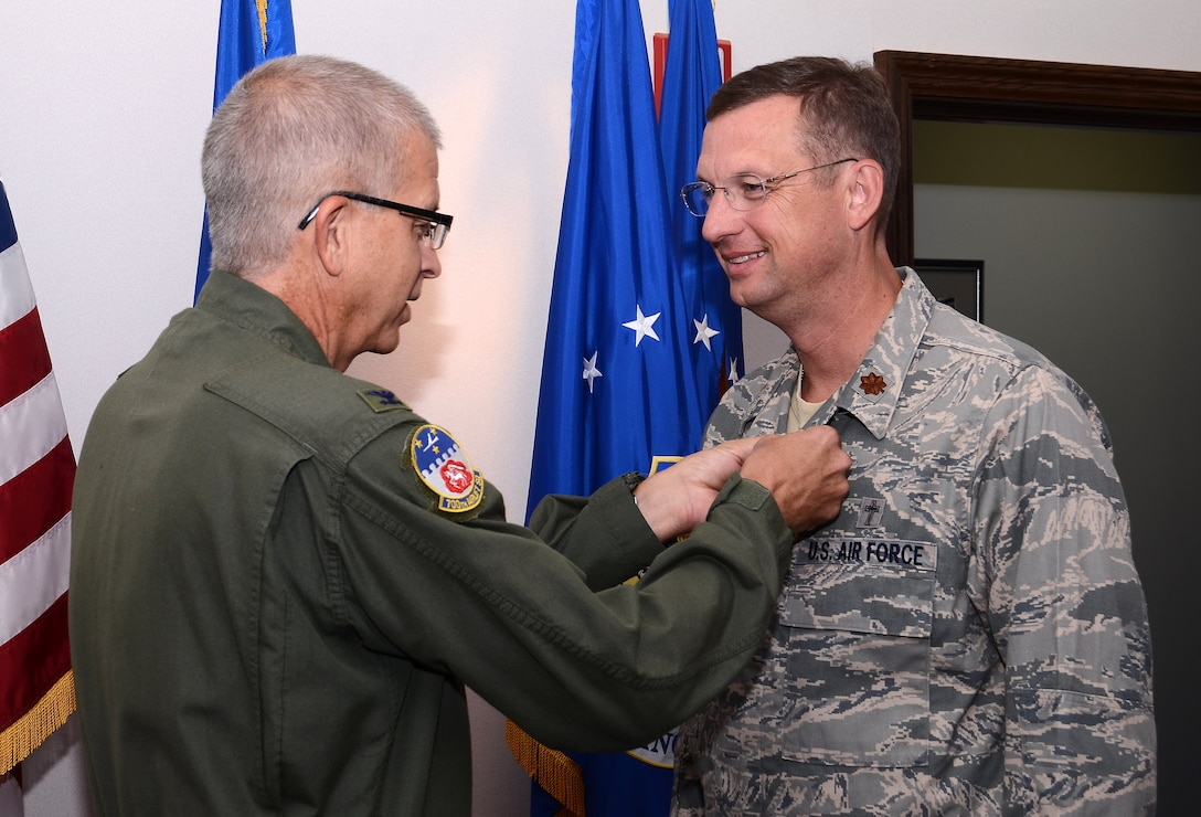 Col. Tim Tarchick, 94th Airlift Wing commander, presents Chaplain (Maj.) Douglas A. Collins with the Meritorious Service Medal, First Oak Leaf Cluster Sept.8 for outstanding professional skill, leadership and ceaseless efforts to support the Airmen and families of the 94th Airlift Wing during his Sept. 9, 2005 to Jan. 2013 tenure.