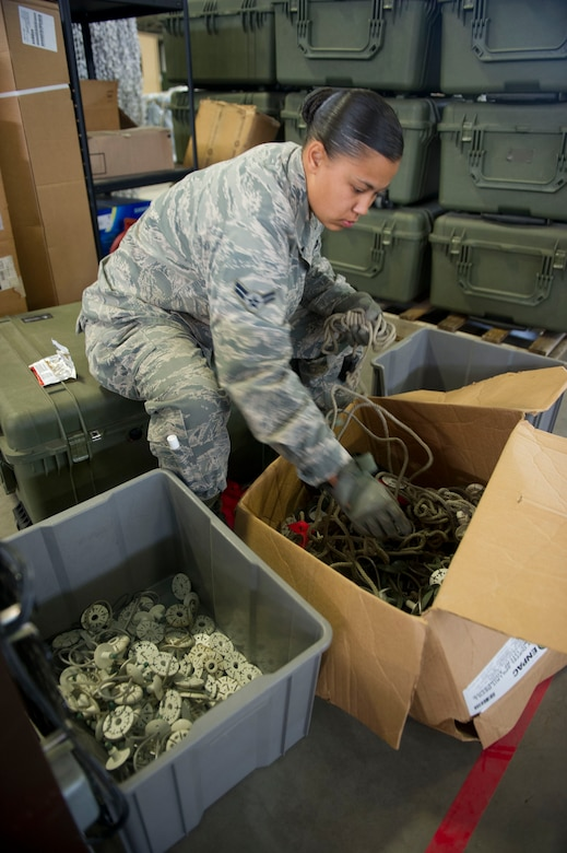 JOINT BASE MCGUIRE-DIX-LAKEHURST, N.J. - Airman 1st Class Ayisha Jones, 819th Global Support Squadron, sorts out equipment to help clean out the Global Reach Deployment Center, here, Aug. 7, 2013. (U.S. Air Force photo by Staff Sgt. Gustavo Gonzalez)
