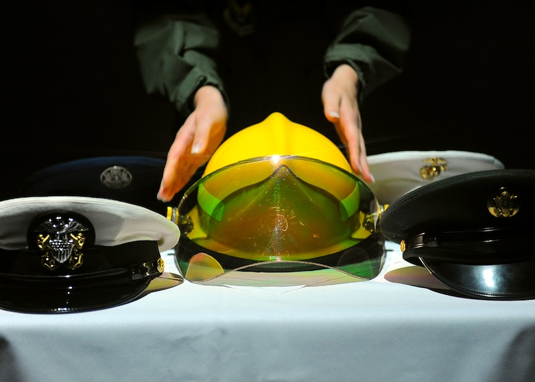 "SPANGDAHLEM AIR BASE, Germany – An instructor from the Kisling NCO Academy places a firefighter helmet on a table during the Air Force Ball Sept. 7, 2013. The service caps represent military heritage and service members killed in action. The instructors performed as ""Spirits of the Past,"" a demonstration of Air Force heritage from World War I to current operations. (U.S. Air Force photo by Staff Sgt. Daryl Knee/Released)"