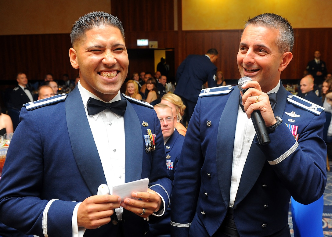 SPANGDAHLEM AIR BASE, Germany – U.S. Air Force 1st Lt. Jeffrey Rodriguez, 52nd Component Maintenance Squadron and one of the master of ceremonies, talks with 52nd Fighter Wing Commander Col. David Julazadeh during the Spangdahlem Air Force Ball at Club Eifel Sept. 7, 2013. Rodriguez had targeted people in the audience to stand and give examples of important people in Air Force history. (U.S. Air Force photo by Staff Sgt. Daryl Knee/Released)