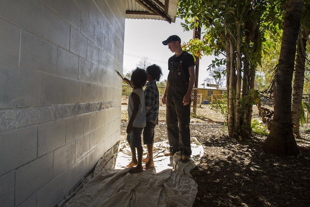 Jeffrey Pierce, an aircrew trainee with Marine Aerial Refueler Transport Squadron 152, helps two local children paint a school building in the Jilkminggan community. Although the Marines and sailors began the painting job alone, passing children became curious of the servicemembers and joined in the work.