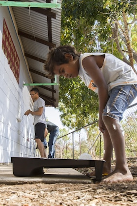 A child from the Jilkminggan community helps Marines and sailors paint a school building during a visit with the Aboriginal community, Aug. 24, 2013. While at Jilkminggan, the servicemembers not only helped improved the community, they also went fishing with the Aboriginals and toured their land.