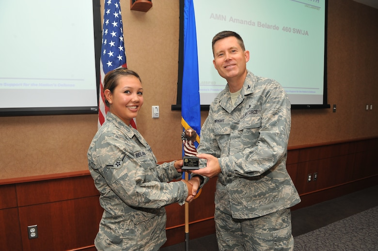 Airman Amanda L. Belarde, Buckley Legal Office military justice paralegal, receives the Airman of the Month Award from Col. Dan Wright, 460th Space Wing commander, Sept. 10, 2013, at Buckley Air Force Base, Colo. Belarde received this award for her exceptional service in courts-martial, successfully completing her Career Development Courses and her work as the Airman Against Drunk Driving vice president. (U.S. Air Force photo by Phillip Houk/Released)