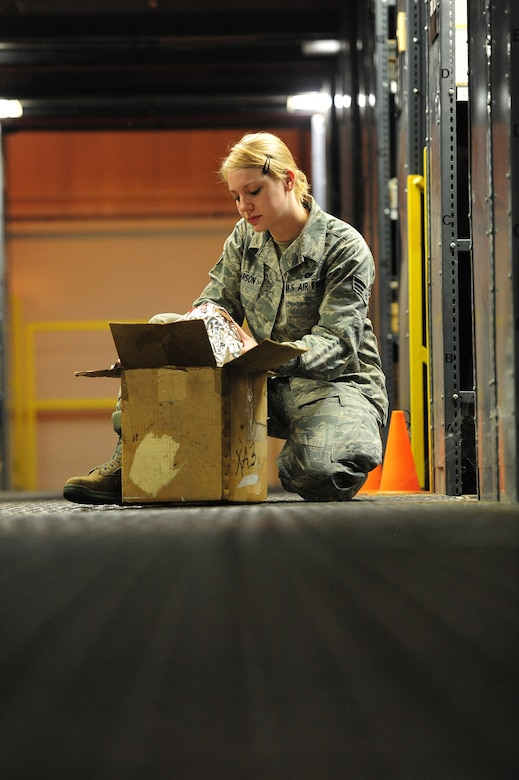 U.S. Air Force Senior Airman Sarah Pearson, 509th Logistics Readiness Squadron aircraft parts journeyman, looks for a stock number on a piece of equipment in the aircraft part store at Whiteman Air Force Base, Mo., Aug. 2, 2013. Without the stock numbers of equipment, Airmen may find it difficult to keep accountability of parts when using their online spreadsheet. (U.S. Air Force photo by Staff Sgt. Nick Wilson/Released)