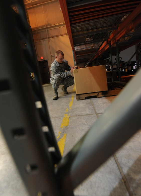U.S. Air Force Airman 1st Class Christopher Neal, 509th Logistics Readiness Squadron aircraft parts journeyman, places a package in its proper location in the aircraft part store at Whiteman Air Force Base, Mo., Aug. 2, 2013. Along with managing a warehouse filled with equipment, aircraft parts journeymen are responsible for providing equipment to Airmen and civilians who work on the flightline. (U.S. Air Force photo by Staff Sgt. Nick Wilson/Released)