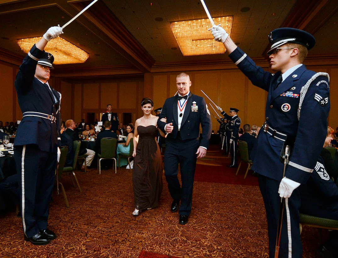 Chief Master Sgt. Eric W. Stere, 22nd Air Force, security forces manager, with wife Amy Stere, pass under the sabre formation during the 2013 Dobbins Chief's Recognition Ceremony held at the Renaissance Waverly Hotel, Atlanta, Ga., Sep. 7. Stere is one of eight chiefs recognized for reaching the highest enlisted grade during the evening's event. (U.S. Air Force photo/Don Peek)