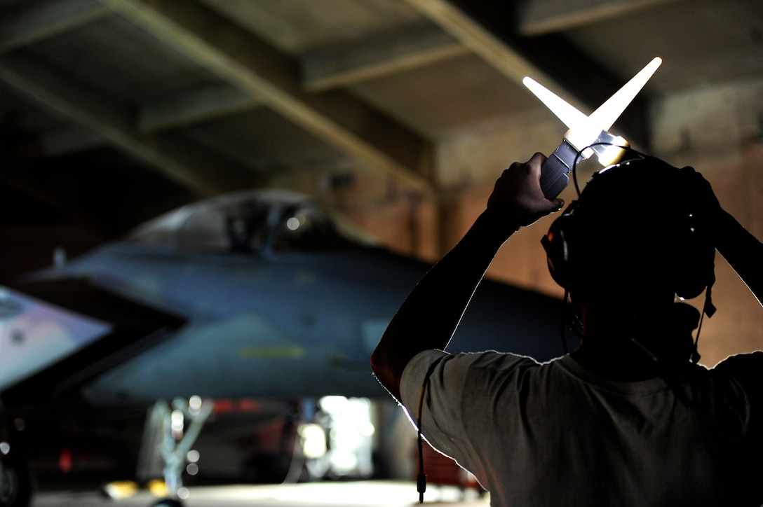 A U.S. Air Force crew chief from the 18th Aircraft Maintenance Squadron prepares to marshal a U.S. Air Force F-15 Eagle onto the flightline during a local operational readiness exercise on Kadena Air Base, Japan, Sept. 9, 2013. The 18th Wing periodically conducts LOREs to maintain proficiency in their capabilities to support the common defense of the Asia-Pacific region. (U.S. Air Force photo by Senior Airman Maeson L. Elleman)