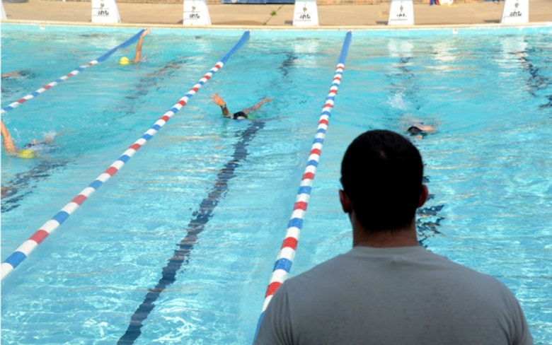 Airman 1st Class Lance Thornton watches his team swim laps at practice Aug. 30. After six months of volunteering with the Montgomery YMCA Barracudas, Thornton became the head coach for the entire program. In this role, Thornton leads the instruction of all of 130 six to 18 year-old swimmers.  (U.S. Air Force photo by Airman 1st Class William Blankenship)