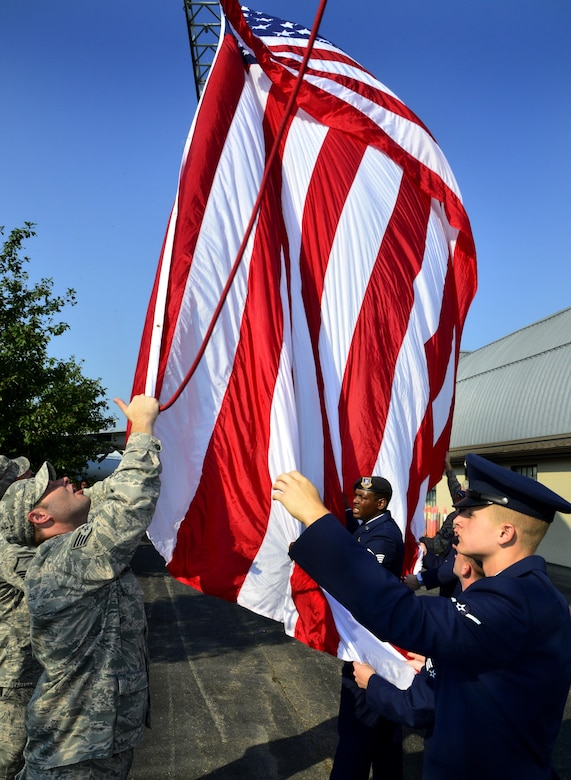 Airmen from the 436th Civil Engineer Squadron and 436th Security Forces Squadron raise the flag in honor of the victims of 9/11, on Sept. 11, 2013, at Dover Air Force Base, Del. The memorial incorporates two pieces of steel from World Trade Center tower one, a rock from the United Airlines Flight 93 crash site and a block from the damaged portion of the Pentagon. (U.S. Air Force photo/David S. Tucker)
