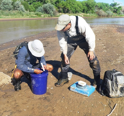 ALBUQUERQUE, N.M., -- Justin Reale (left) and Eric Gonzalez analyze a fish, Aug. 15, 2013.
