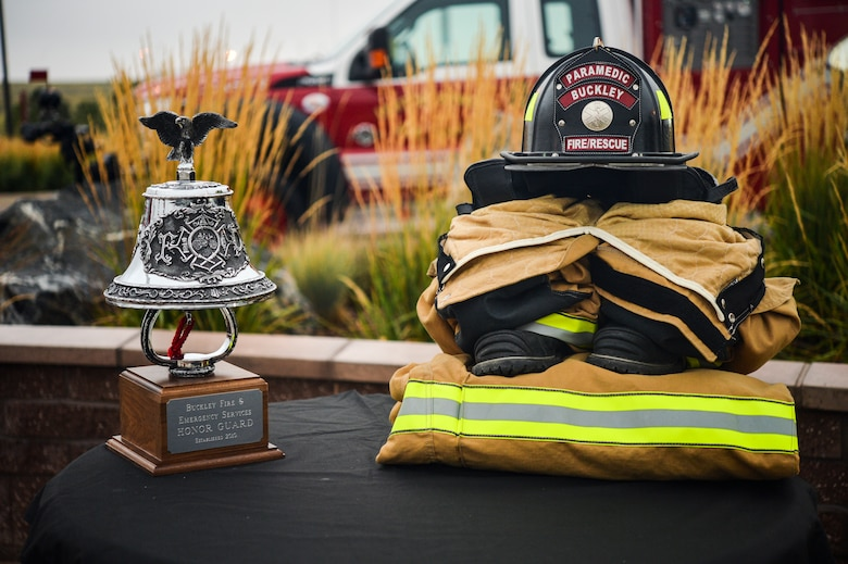 A firefighter's uniform and a ceremonial bell are displayed at the Patriot Day and National Day of Remembrance Sept. 11, 2013 at the 460th Space Wing headquarters building on Buckley Air Force Base, Colo. The symbols were on display to honor the firefighters who lost their lives during the 9/11 attacks on the World Trade Centers in New York. (U.S. Air Force photo by Staff Sgt. Paul Labbe/Released)