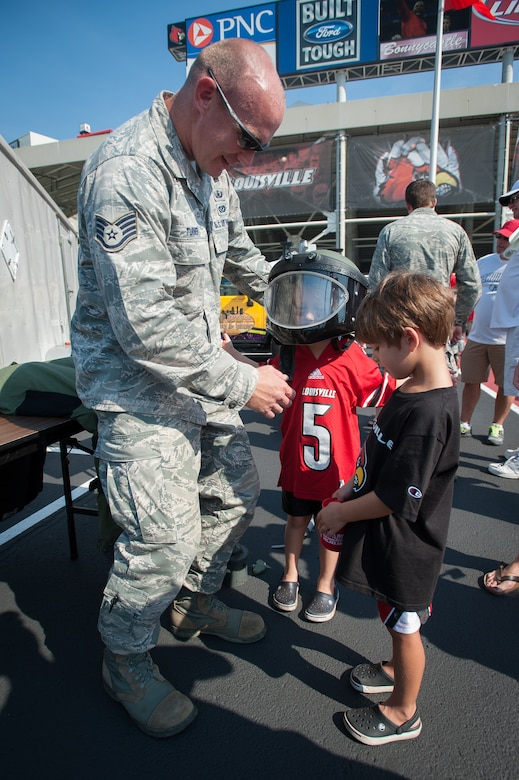 Staff Sgt. Dustin Turner, an explosive ordnance disposal technician with the Kentucky Air National Guard's 123rd Civil Engineer Squadron, helps a boy try on the helmet from a protective bomb suit as part of a static display of EOD equipment prior to the University of Louisville-Eastern Kentucky University football game at Papa John's Cardinal Stadium in Louisville, Ky., Sept. 7, 2013. U of L billed the game as Military Appreciation Day. (U.S. Air National Guard photo by Maj. Dale Greer)