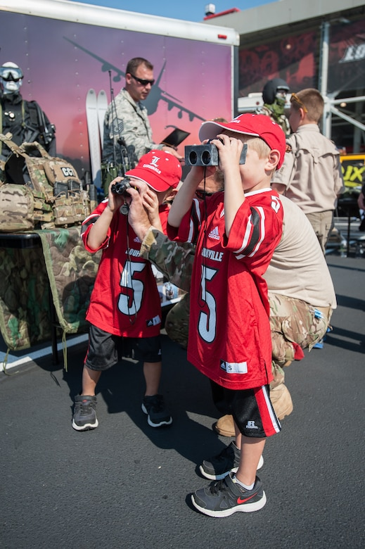 Two boys try out digital rangefinders as part of a static display of Kentucky Air National Guard special tactics equipment prior to the University of Louisville-Eastern Kentucky University football game at Papa John's Cardinal Stadium in Louisville, Ky., Sept. 7, 2013. U of L billed the game as Military Appreciation Day. (U.S. Air National Guard photo by Maj. Dale Greer)